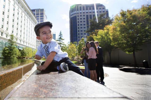 Un petit garçon joue près de la fontaine de temple square près du centre de conférence.
