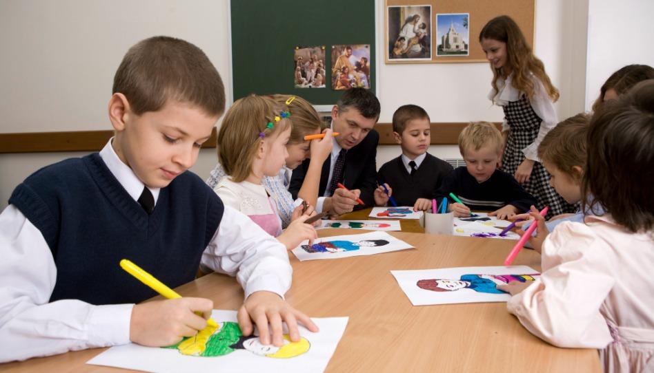 un instructeur de la primaire avec sa classe: ils colorient après la leçon