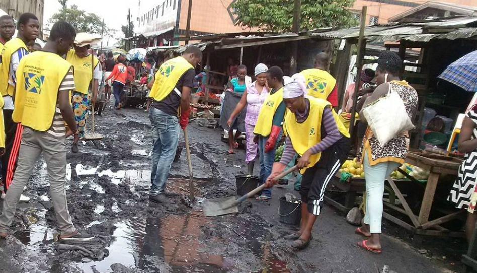 les mains serviables nettoient le marché de Douala