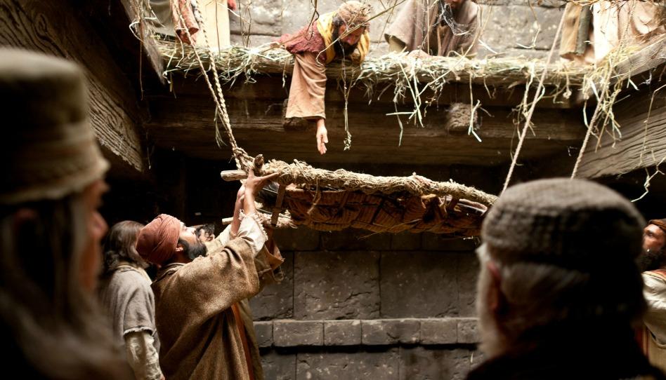 un homme paralysé est descendu sur un brancard par le toit, près de Jésus