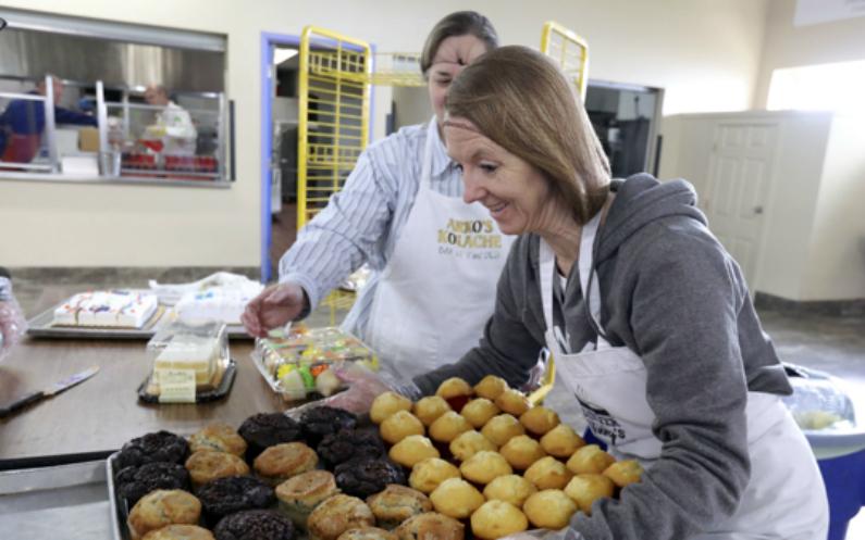 Bénévole avec un plateau de muffins